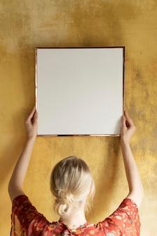 Mulher pendurando uma maquete de moldura em uma parede amarela de grunge
