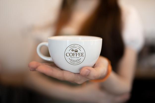 Mulher segurando a maquete da caneca de café