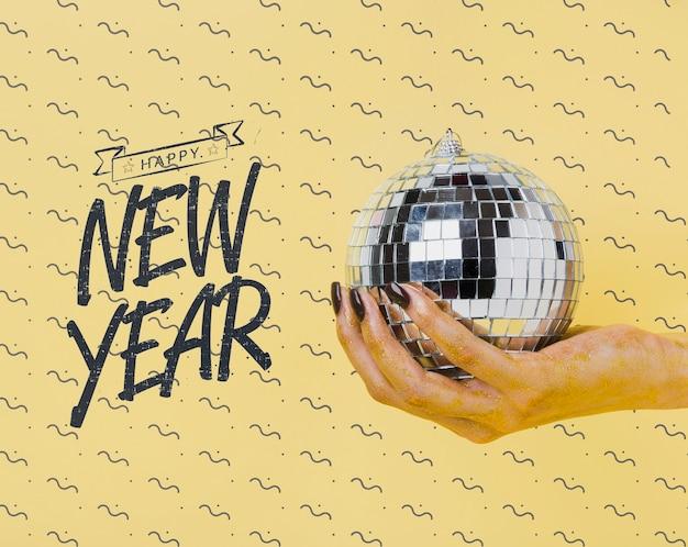 Mulher segurando bola de discoteca com letras de ano novo