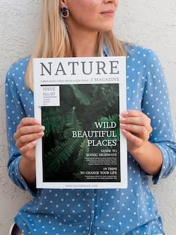 Mulher segurando com as duas mãos uma revista de natureza