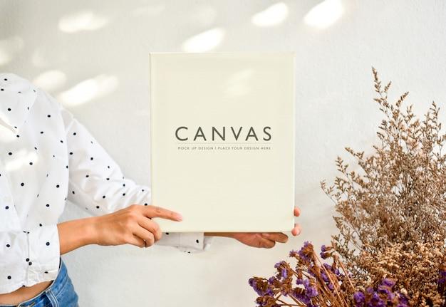 Mulher segurando mock imagem desenhada cacto de quadro de lona.