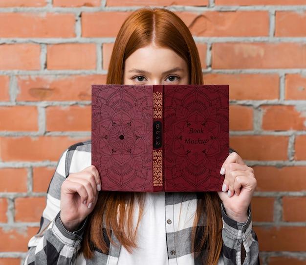 Mulher segurando o modelo de livro
