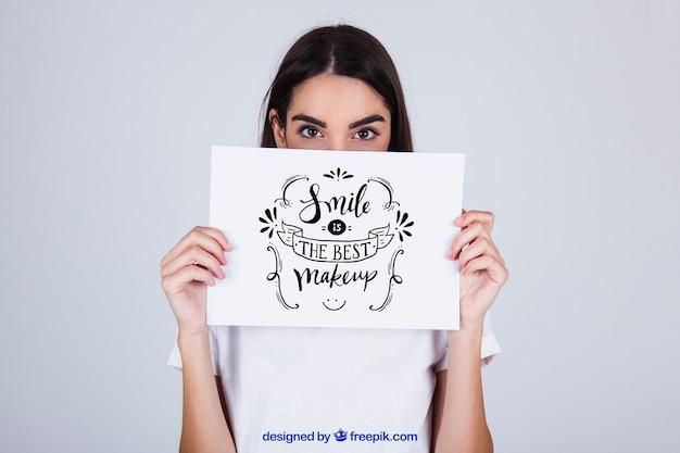 Mulher segurando papel com mensagem na frente do rosto
