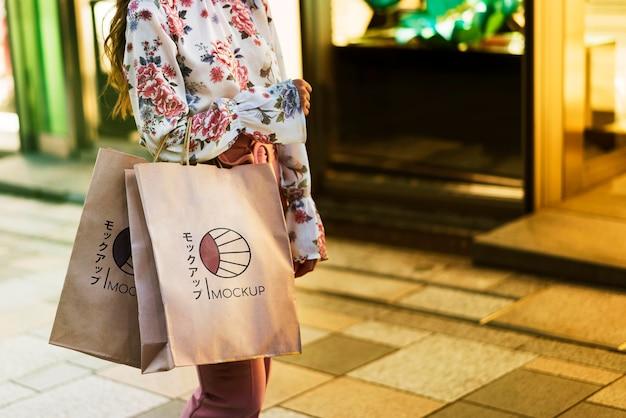 Mulher segurando sacolas de compras na rua