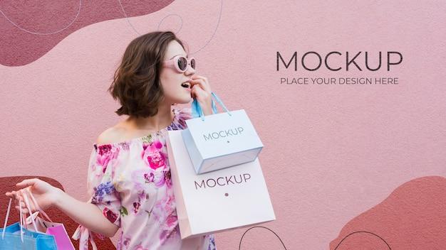 Mulher segurando sacolas de papel de modelo
