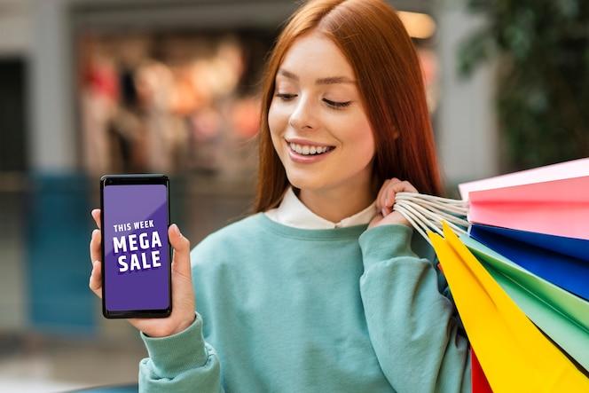 Mulher segurando sacos de papel e olhando para o celular