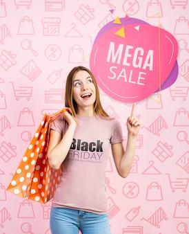 Mulher segurando sacos de papel e vestindo uma camiseta preta de sexta-feira