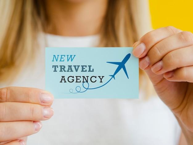Mulher segurando um cartão de agência de viagens
