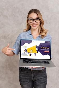 Mulher segurando um laptop e apontando para ele
