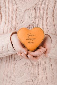 Mulher segurando um pequeno coração artesanal