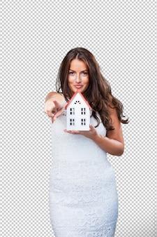 Mulher segurando uma casa e apontando para a frente