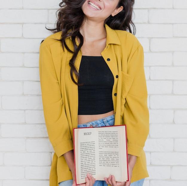 Mulher segurando uma maquete de livro