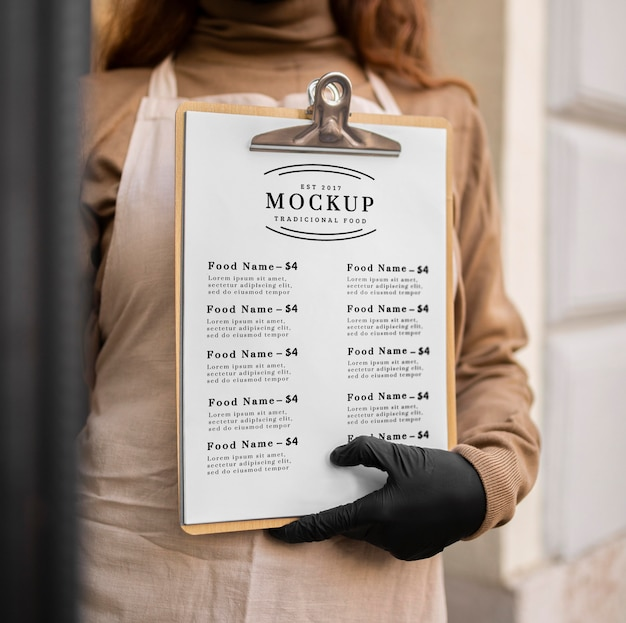 Mulher segurando uma maquete de menu de restaurante na área de transferência