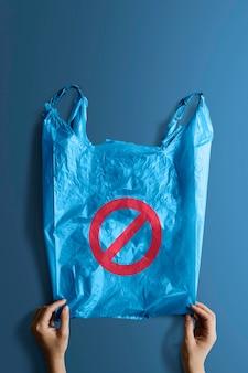 Mulher segurando uma maquete de saco plástico azul com uma placa de proibição
