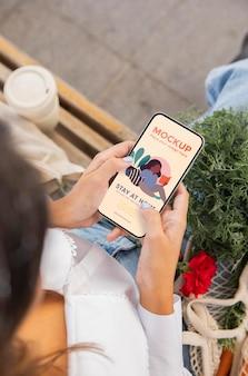 Mulher segurando uma maquete de smartphone