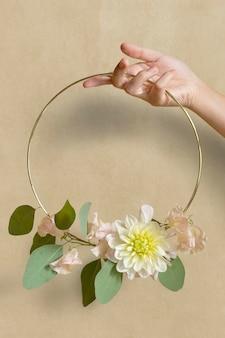 Mulher segurando uma moldura dourada decorada com flores