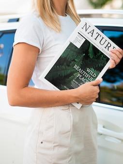 Mulher segurando uma revista ao lado de um carro simulado