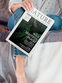 Mulher segurando uma revista de natureza ao lado de sua perna