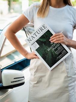 Mulher segurando uma revista de natureza ao lado de um carro