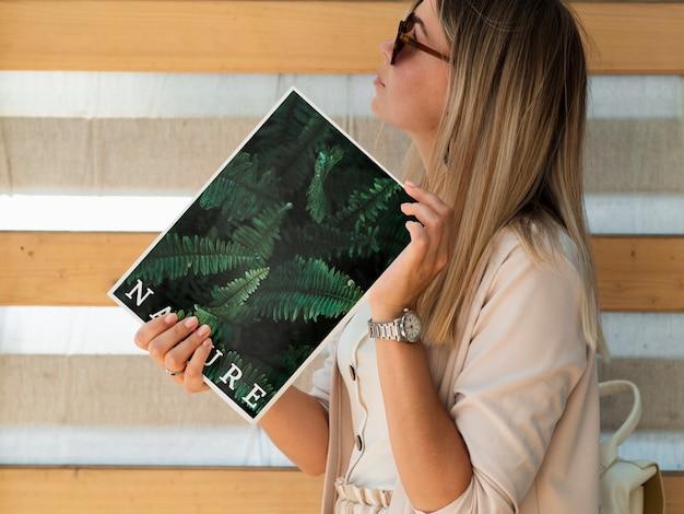 Mulher segurando uma revista e olhando para longe simulado