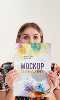 Mulher segurando uma revista mock e olhando para a câmera