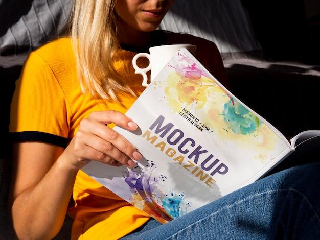 Mulher segurando uma revista mock e uma caneca