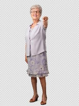 Mulher sênior de corpo inteiro alegre e sorridente apontando para a frente