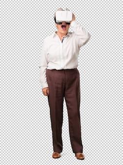 Mulher sênior de corpo inteiro animada e entretida, jogando com óculos de realidade virtual, explorando um mundo de fantasia, tentando tocar algo