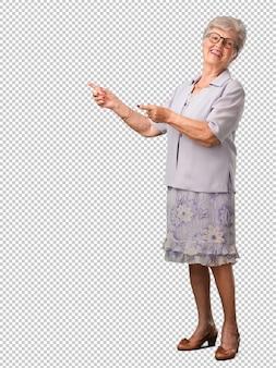 Mulher sênior de corpo inteiro, apontando para o lado, sorrindo surpreso apresentando algo