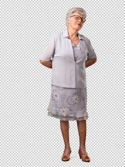 Mulher sênior de corpo inteiro com dor nas costas devido ao estresse do trabalho, cansado e astuto