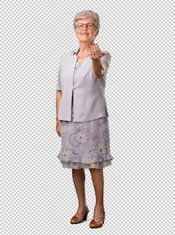 Mulher sênior de corpo inteiro, convidando para vir, confiante e sorridente, fazendo um gesto com a mão, sendo positivo e amigável