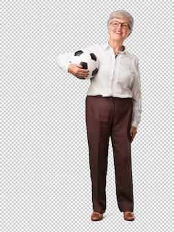 Mulher sênior de corpo inteiro sorrindo e feliz, segurando uma bola de futebol, atitude competitiva