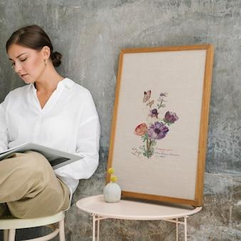 Mulher sentada em um banquinho lendo um livro perto de uma moldura de foto