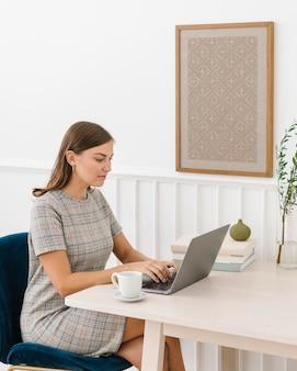 Mulher sentada em uma cadeira perto de uma moldura na parede branca