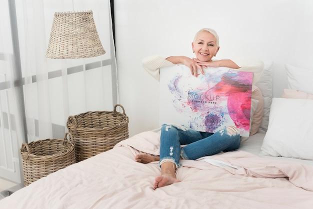 Mulher sentada na cama e segurando uma faixa de maquete