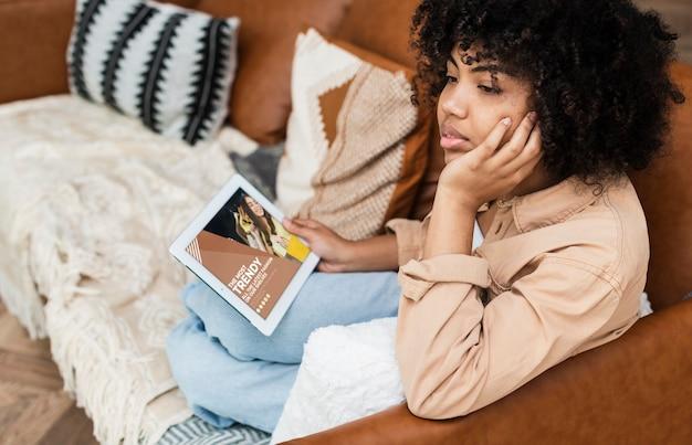 Mulher sentada no sofá com o tablet na mão e olhando para longe