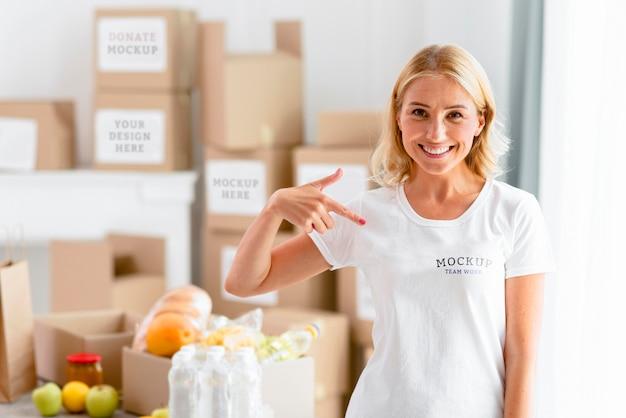 Mulher sorridente apontando para sua camiseta