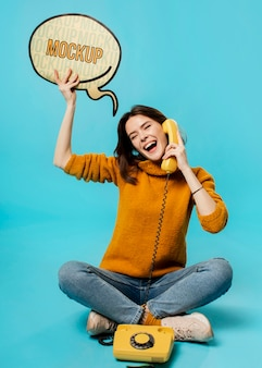 Mulher sorridente com bolha de bate-papo e telefone antigo