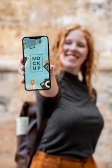Mulher sorridente com foto média segurando o telefone