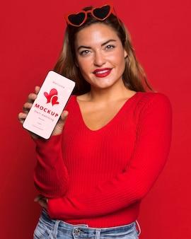 Mulher sorridente de tiro médio segurando um smartphone
