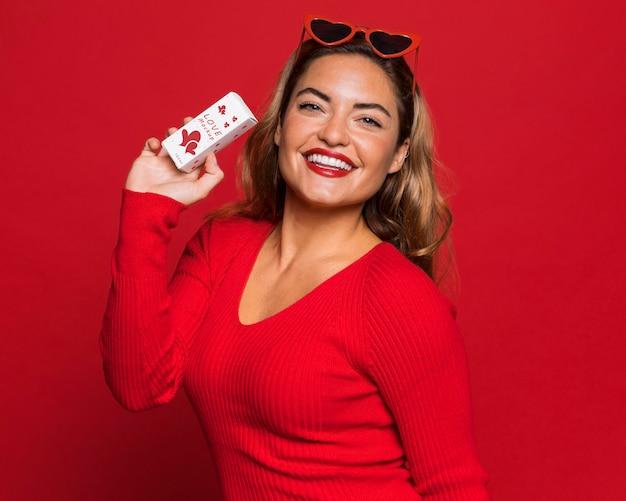 Mulher sorridente de tiro médio segurando uma pequena caixa