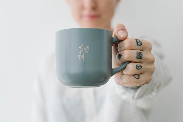 Mulher sorridente e tatuada tomando uma xícara de café