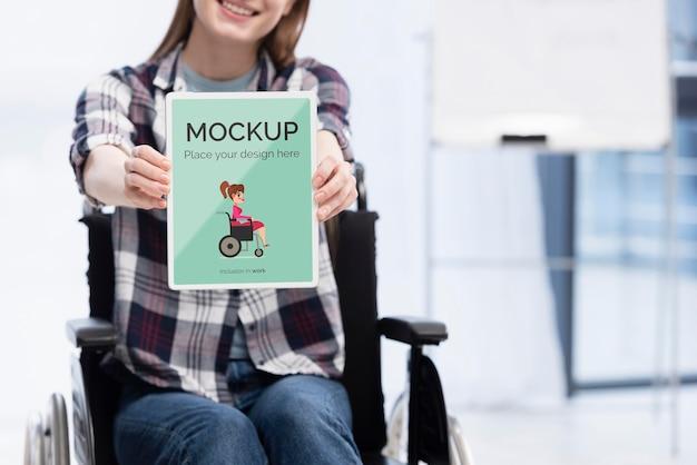 Mulher sorridente em cadeira de rodas trabalhando com espaço de cópia
