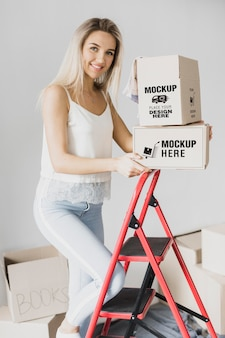 Mulher sorridente segurando caixas