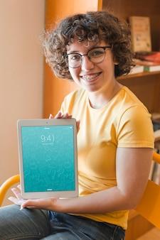 Mulher sorridente, segurando, tabuleta, maquete, em, biblioteca