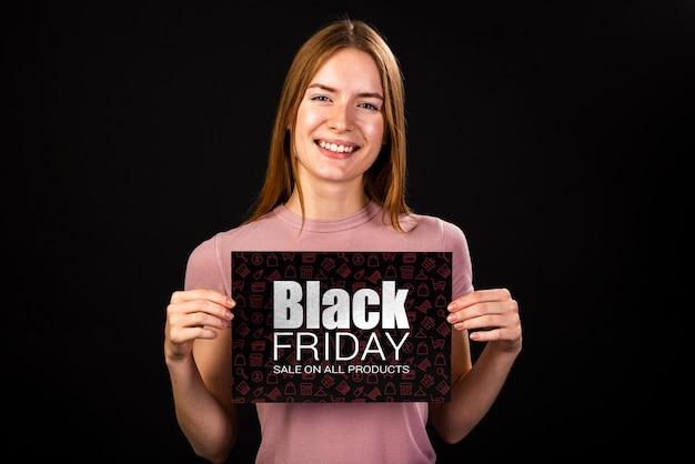 Mulher sorridente segurando uma faixa preta de sexta-feira