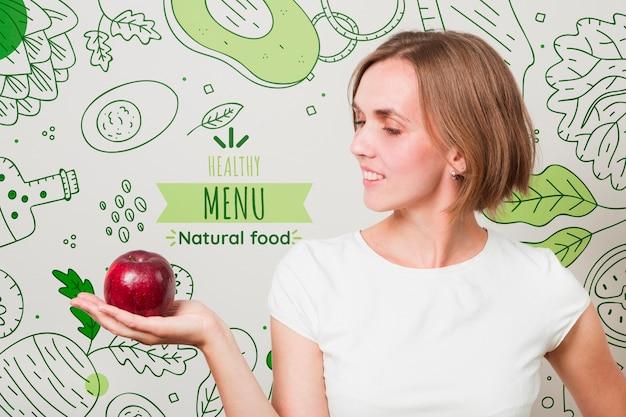 Mulher sorridente, segurando uma maçã