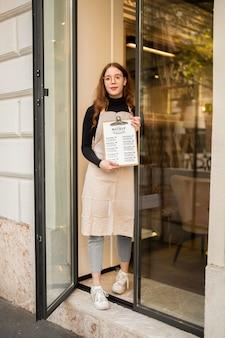 Mulher sorridente trabalhando em um restaurante segurando um menu