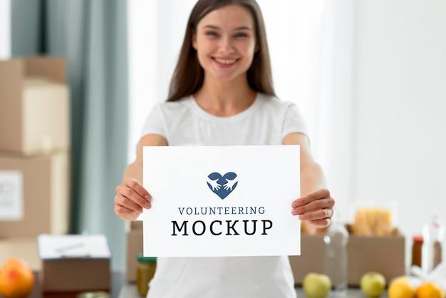 Mulher sorridente, voluntária, segurando um papel em branco