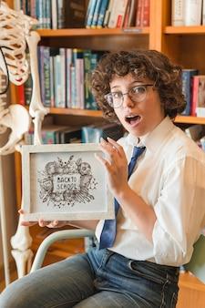 Mulher surpreendida segurando maquete de quadro na biblioteca
